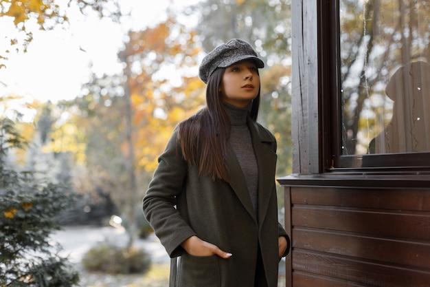 Stilvolles und junges mädchen in einem grauen mantel und in der stilvollen mütze steht an einem herbstnachmittag im park. schöne frau