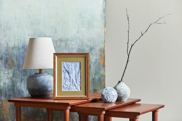 Stilvolles und luxuriöses interieur mit braunem posterrahmen, vasen, büchern, holzhockern, becher und eleganten accessoires in der wohnkultur. vorlage.