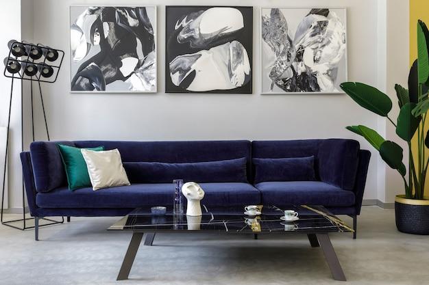 Stilvolles und modernes wohnzimmerinterieur mit blauem samtsofa, gemälden, schwarzer designlampe, pflanze, tisch und dekoration, betonboden