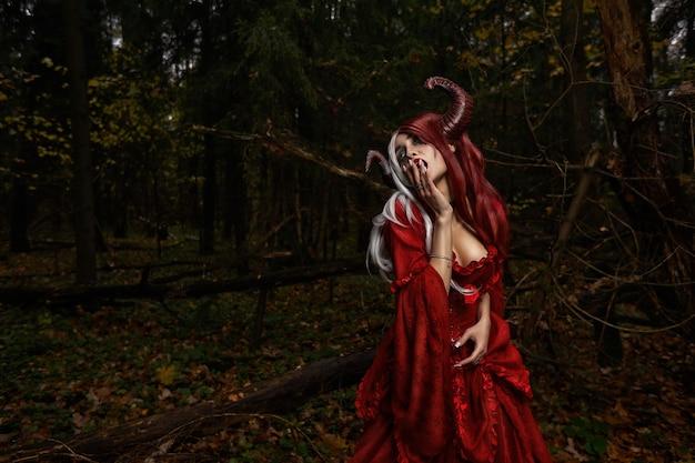 Stilvolles und modisches modellmädchen im bild von maleficent, das unter mystischem wald posiert - märchengeschichte, cosplay. halloween.