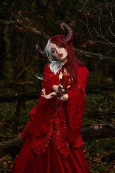 Stilvolles und modisches modellmädchen im bild von maleficent, der unter mystischem wald aufwirft - märchengeschichte, cosplay