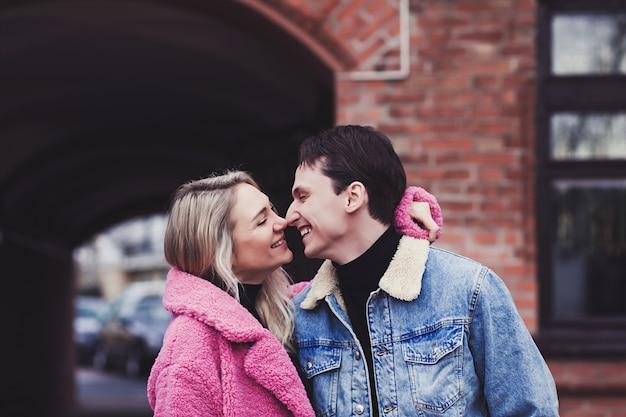 Stilvolles und romantisches kaukasisches paar, das in stadtstraße küsst