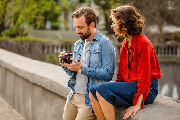 Stilvolles verliebtes paar, das auf romantischer reise in der straße sitzt und foto macht Kostenlose Fotos