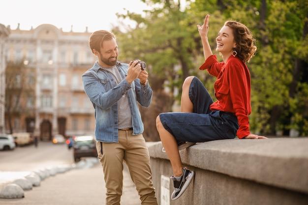Stilvolles verliebtes paar, das auf romantischer reise in der straße sitzt und foto macht