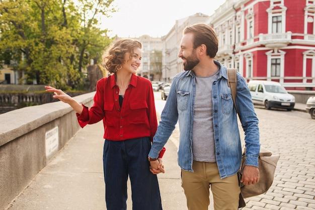 Stilvolles verliebtes paar, das auf romantischer reise in der straße sitzt
