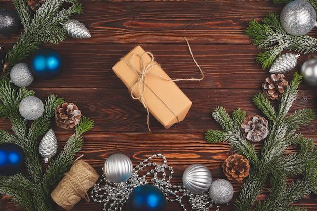 Stilvolles verziertes weihnachtsgeschenk mit band auf hölzernem hintergrund, draufsicht