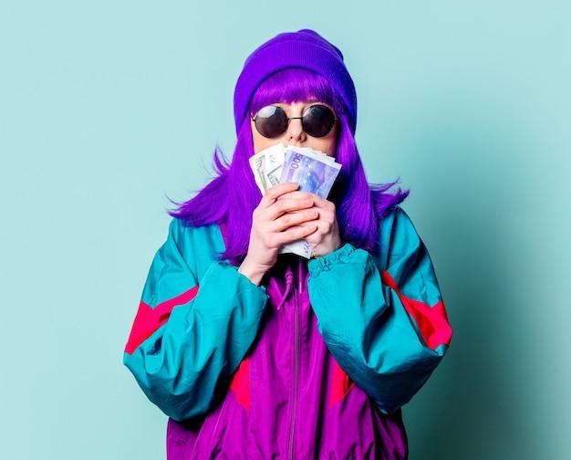Stilvolles weißes mädchen mit lila haaren und trainingsanzug halten bargeld an der blauen wand