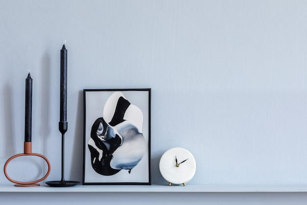 Stilvolles wohnzimmer-interieur in eleganter wohnung mit rahmen, weißer uhr, kerzen, grauer holzvertäfelung und eleganten accessoires im regal in moderner home-staging.