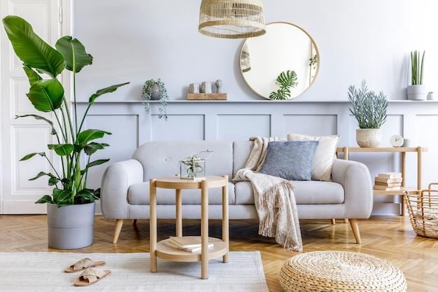 Stilvolles wohnzimmer-interieur mit grauem design-sofa, couchtisch, rattan-puff, korb, regal, spiegel, tropischen pflanzen, dekoration, teppich und eleganten persönlichen accessoires in moderner wohnkultur.