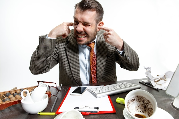 Stimmen in seinem kopf. junger mann, der unter den gesprächen der kollegen im büro leidet. ich kann mich nicht konzentrieren und in der stille arbeiten. konzept der probleme, des geschäfts, der probleme und des stresses der büroangestellten.
