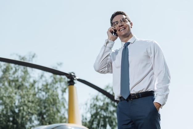 Stimmungsaufhellender chat. angenehmer junger geschäftsmann, der am telefon plaudert und hell lächelt, während er an einem hubschrauberlandeplatz steht