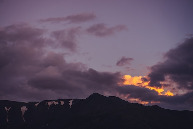 Stimmungsvolle berglandschaft mit lila morgenhimmel. malerische landschaft mit felsen mit schnee unter lila sonnenunterganghimmel. schöner sonnenaufgang in den bergen in pastelltönen. leuchtende farbe im bewölkten himmel der morgendämmerung.