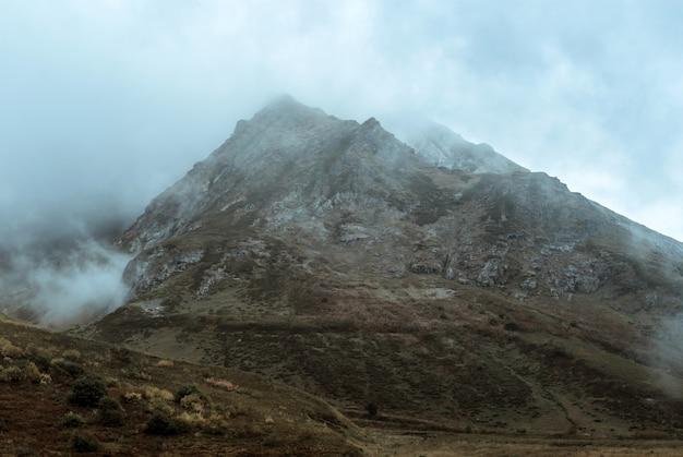 Stimmungsvolle graue düstere berglandschaft mit einem felsigen grat zwischen den wolken