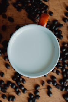 Stimmungsvolle tasse milch mit kaffeekörnern