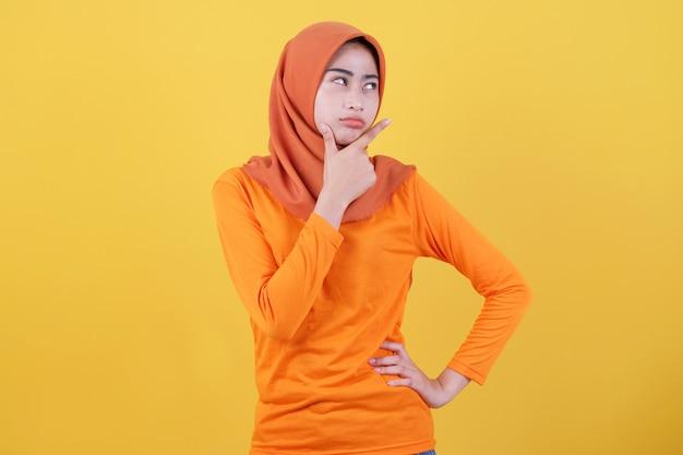 Stimmungsvolle unzufriedene asiatin, die hijab trägt und schmollend verärgert verärgert die stirn runzelt und eine grimasse zeigt, die haltung zeigt, die enttäuscht unzufrieden steht
