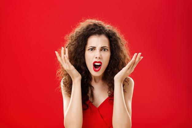 Stimmungsvolle unzufriedene und wütende reiche frau, die mit einem schrecklichen chipgeschenk unzufrieden ist, das frustriert die handflächen hebt und ahnungslose gesten streitet und vor empörung schreit, die in einem roten eleganten kleid steht. platz kopieren