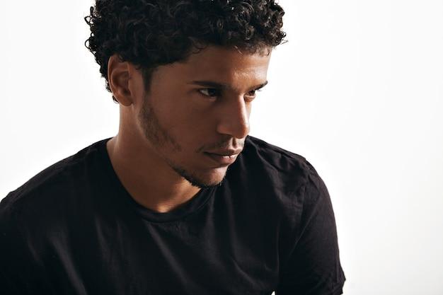 Stimmungsvolles nachdenkliches schwarzes junges modell, das ein leeres schwarzes t-shirt trägt, das auf weiß lokalisiert wird