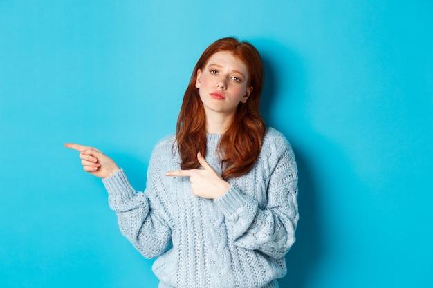 Stimmungsvolles teenager-mädchen mit roten haaren, das mit den fingern nach links auf das logo zeigt, belästigt und gelangweilt starrt, auf blauem hintergrund stehend.
