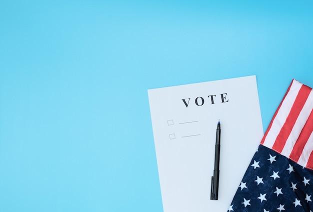 Stimmzettel mit stift und flagge auf blauem hintergrund. treffen sie ihr wahlkonzept. flache lage, kopierraum.