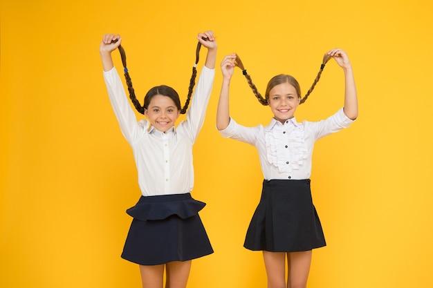 Stimulans für langes haarwachstum. nette kleine kinder, die lange haarzöpfe auf gelbem hintergrund halten. entzückendes kleines mädchen, das auf langes haar stolz ist. das tragen von langen haaren in zöpfen für die schule.