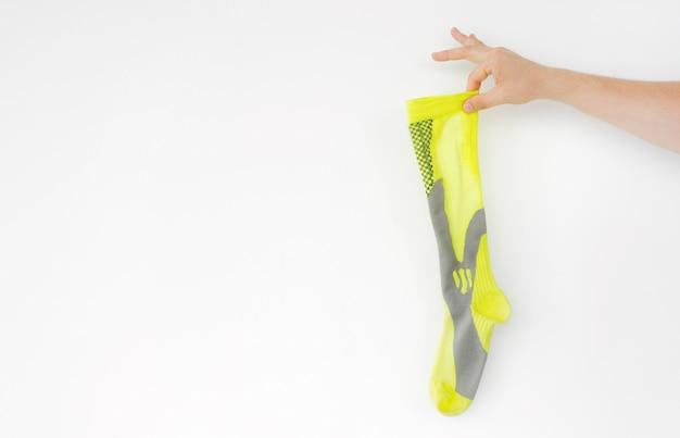 Stinkende gelbe laufsportsocke in der hand isoliert