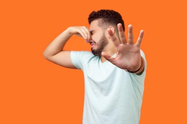 Stinkender geruch. seitenansicht eines verwirrten brünetten mannes mit bart in weißem t-shirt, der den atem mit den fingern auf der nase anhält, angewidert von schlechtem geruch, furz, gestikulierend aufhören. studioaufnahme isoliert auf orangem hintergrund