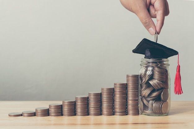 Stipendium geld konzept. hand des mannes münzen in glas mit geldstapel setzend