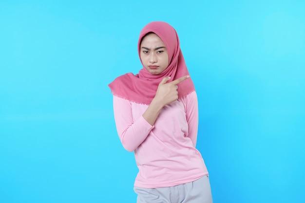 Stirnrunzeln asiatische frau mit ihrem fingerzeig isoliert auf hellblauem hintergrund trägt hijab mit rosa t-shirt