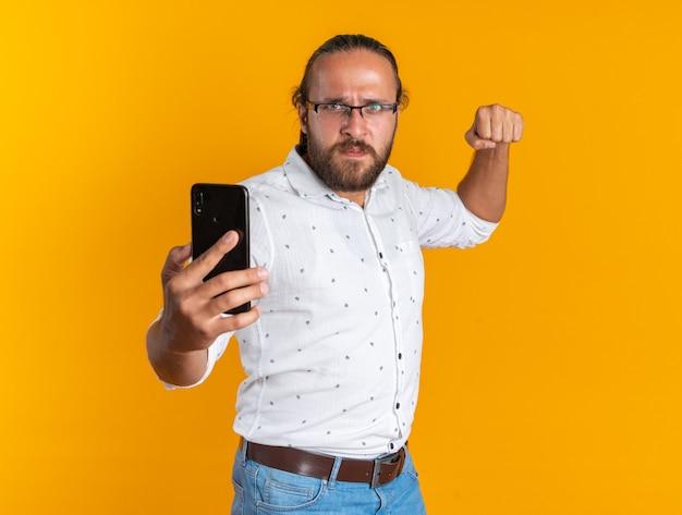 Stirnrunzelnd erwachsener gutaussehender mann mit brille, der das handy in richtung der kamera ausstreckt, die faust zeigt