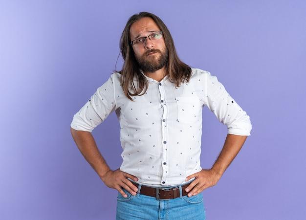 Stirnrunzelnd erwachsener gutaussehender mann mit brille, der die hände an der taille hält