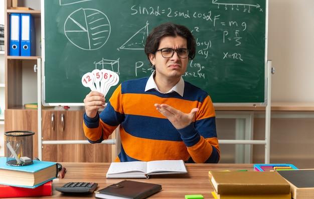 Stirnrunzelnd junger geometrielehrer mit brille, der am schreibtisch mit schulmaterial im klassenzimmer sitzt und nach vorne schaut und zahlenfans zeigt, die auf sie zeigen?