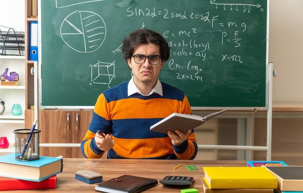 Stirnrunzelnd junger kaukasischer geometrielehrer mit brille am schreibtisch sitzend mit schulwerkzeugen im klassenzimmer mit notizblock und stift