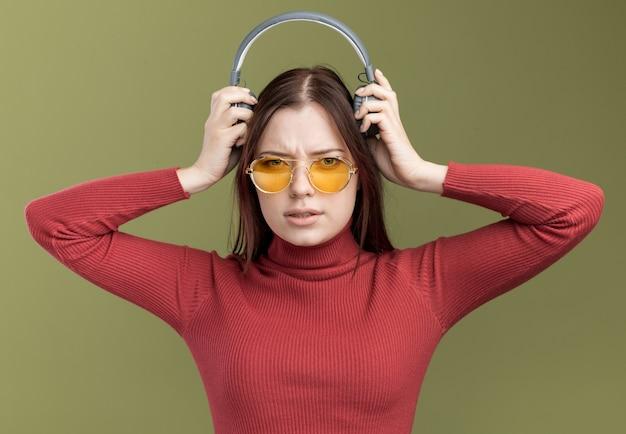 Stirnrunzelnd junges hübsches mädchen mit sonnenbrille, das kopfhörer abnimmt