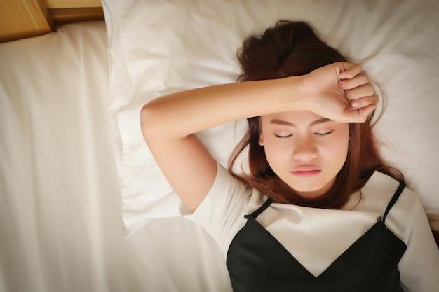 Stirnrunzelnd kranke müde erschöpfte unruhige frau, die mit der hand zur stirn schläft konzept von krankheit, kopfschmerzen, kater, stress