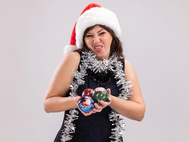 Stirnrunzelnde frau mittleren alters mit weihnachtsmütze und lametta-girlande um den hals mit weihnachtskugeln, die isoliert auf weißem hintergrund in die kamera schaut