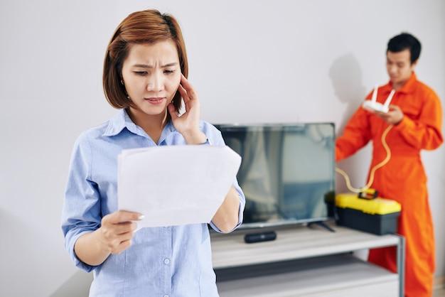 Stirnrunzelnde hausfrau, die rechnung für service des technikers betrachtet, der wi-fi-router in ihrer wohnung installiert