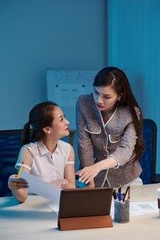 Stirnrunzelnde junge asiatische geschäftsfrau, die kollegin bittet, ihr dokument mit dem layout der mobilen anwendungsschnittstelle zu zeigen, wenn sie spät in der nacht wegen der frist im büro arbeitet