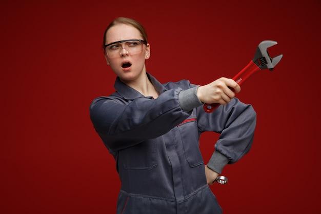 Stirnrunzelnde junge blonde ingenieurin trägt uniform und schutzbrille mit schraubenschlüsseln und hält die hand auf der taille, die mit dem schraubenschlüssel auf die seite schaut und zeigt
