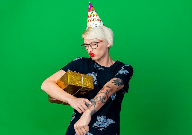 Stirnrunzelnde junge blonde partyfrau, die brille und geburtstagskappe hält, die geschenkbox hält, die sie spät ist geste mit geschlossenen augen lokalisiert auf grüner wand mit kopienraum