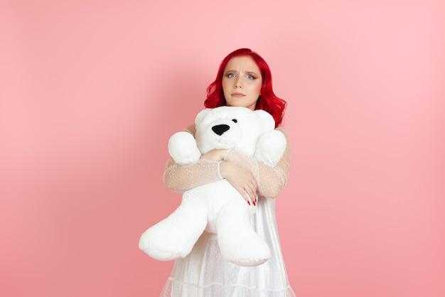 Stirnrunzelnde junge frau in einem weißen kleid und mit roten haaren umarmt einen großen weißen teddybär