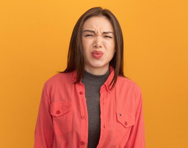 Stirnrunzelnde junge hübsche frau, die die lippen isoliert auf orangefarbener wand schürzt