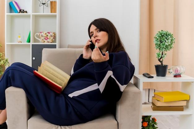 Stirnrunzelnde junge hübsche kaukasische frau, die auf sessel in entworfenem wohnzimmer schaut und zeigt, das am telefon mit buch auf beinen spricht