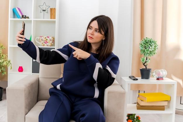 Stirnrunzelnde junge hübsche kaukasische frau, die auf sessel in entworfenem wohnzimmer sitzt, zeigt auf telefon und nimmt selfie