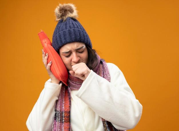 Stirnrunzelnde junge kranke frau, die robe wintermütze und schal berührt kopf mit heißem wasserbeutel hustend hält faust in der nähe des mundes mit geschlossenen augen isoliert auf orange wand