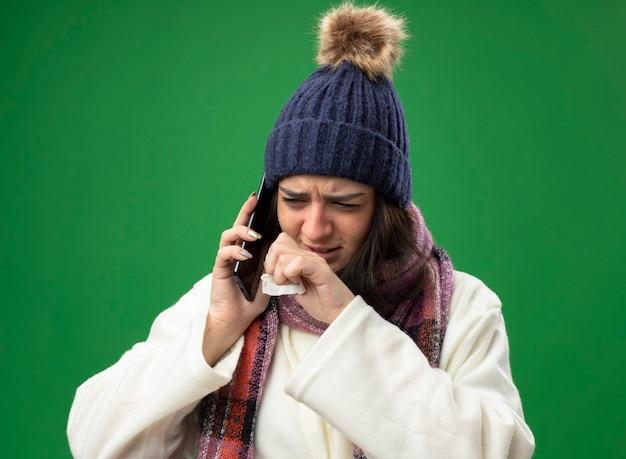 Stirnrunzelnde junge kranke frau, die robe wintermütze und schal spricht am telefon hält serviette hält hand in der nähe des mundes und betrachtet seite lokalisiert auf grüner wand