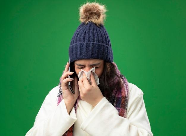 Stirnrunzelnde junge kranke frau, die robe wintermütze und schal trägt, spricht am telefon, das nase mit serviette mit geschlossenen augen abwischt, die auf grüner wand lokalisiert werden