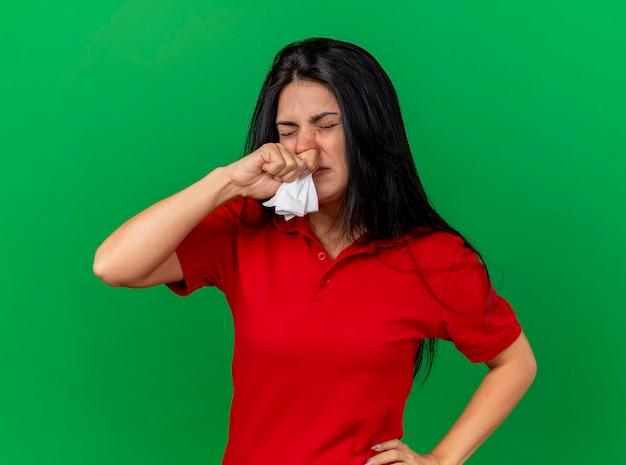 Stirnrunzelnde junge kranke frau, die serviette hält, die hand auf taille setzt, die nase mit geschlossenen augen wischt, die auf grüner wand lokalisiert werden