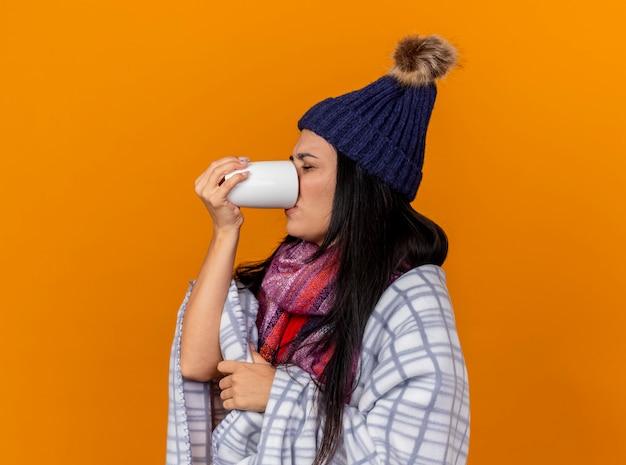 Stirnrunzelnde junge kranke frau, die wintermütze und schal wickelt, die im plaid eingewickelt stehen, das in der profilansicht trinkt tasse des tees mit geschlossenen augen, die auf orange wand lokalisiert werden