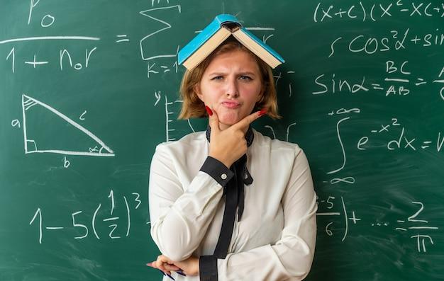 Stirnrunzelnde junge lehrerin, die vor der tafel steht, bedeckt den kopf mit buch im klassenzimmer