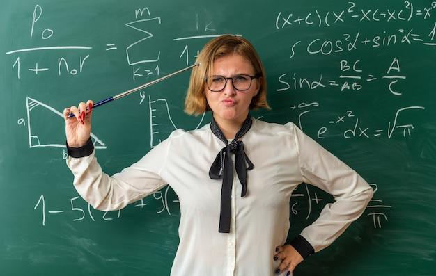 Stirnrunzelnde junge lehrerin, die vor der tafel steht und den zeiger im klassenzimmer auf dem kopf hält